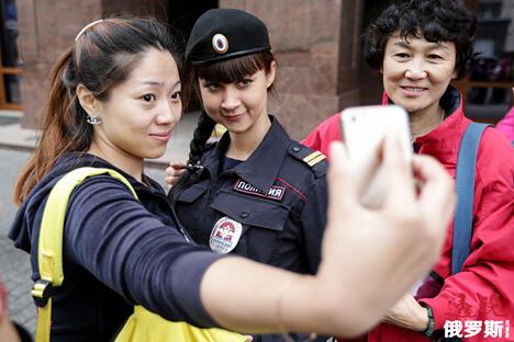 2014年7月,在外国游客聚集的莫斯科老城区步行街出现了一批新的执勤警察——旅游警察。图中:几位中国游客正与一位女性旅游警察合影留念。图片来源:俄通社-塔斯社