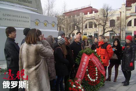 """仪式参加者在""""俄罗斯文化中心敬献""""花篮前留影。图片来源:PressPhoto"""