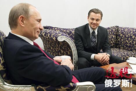 Vladimir Putin (L) listens to actor Leonardo DiCaprio CN