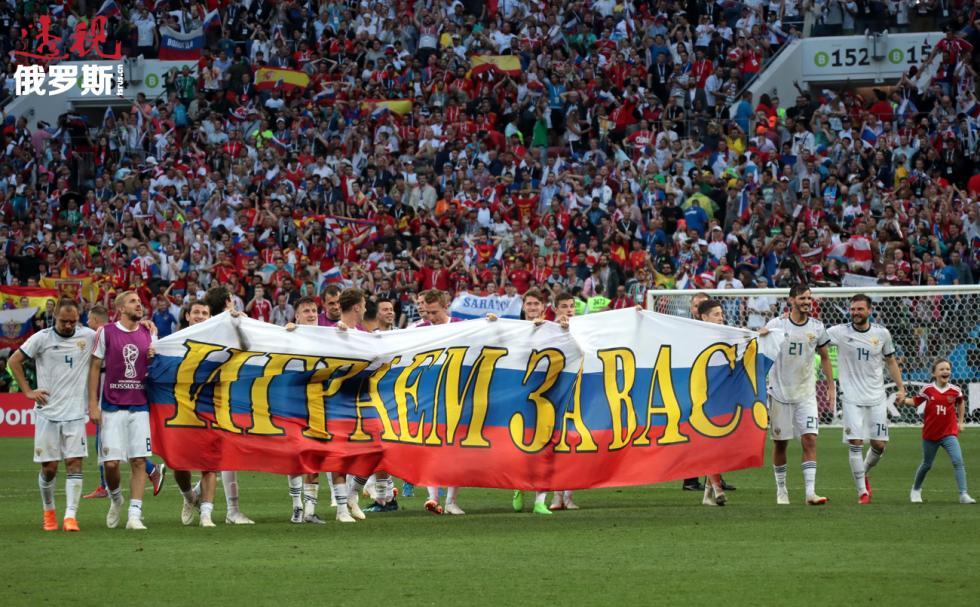 """俄罗斯足球员带着""""我们为你们踢球""""大旗。 图片来源:Vitaly Belousov / 俄新社"""