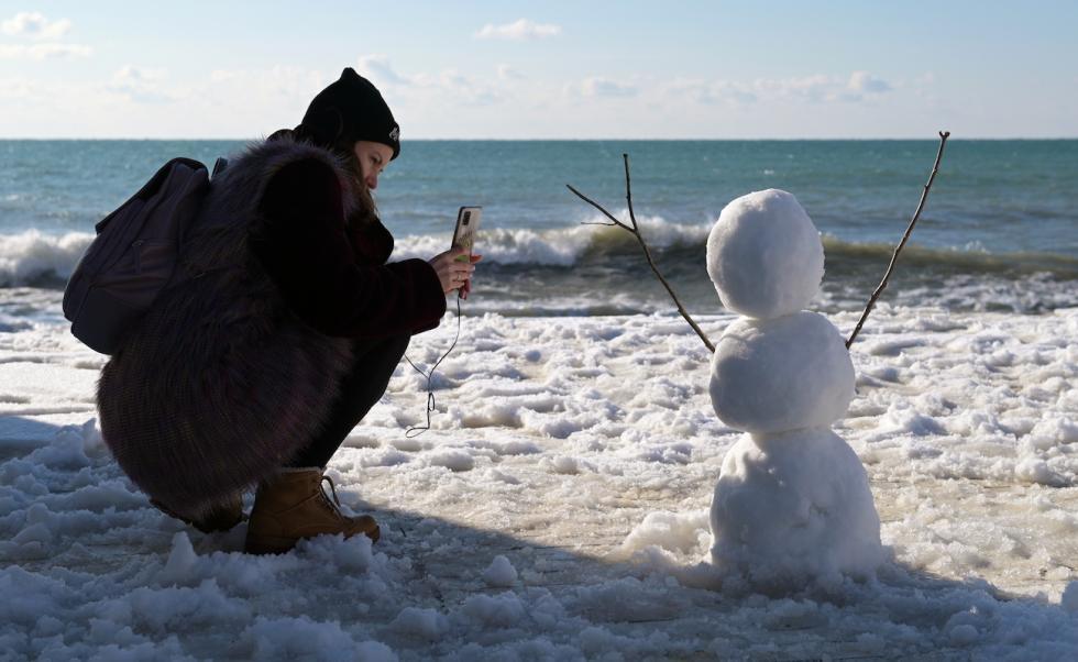 俄罗斯索契市,一位女孩在沙滩上拍雪人 。Artur Lebedev/俄新社